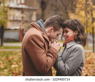 Young couple in love holding hands and walking through a park on a sunny autumn day.