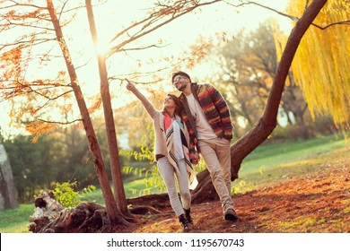 Young couple in love holding hands and walking through a park on a sunny autumn day