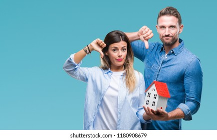Young couple in love holding house over isolated background with angry face, negative sign showing dislike with thumbs down, rejection concept