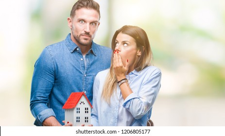 Young couple in love holding house over isolated background cover mouth with hand shocked with shame for mistake, expression of fear, scared in silence, secret concept