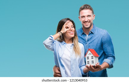 Young couple in love holding house over isolated background with happy face smiling doing ok sign with hand on eye looking through fingers