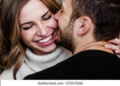 Young couple in love hug each other on the black background