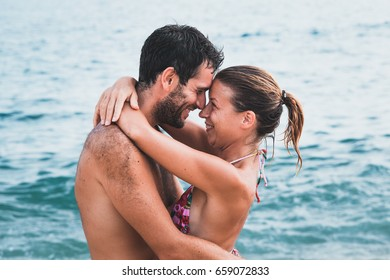 Young couple in love hugging at the beach