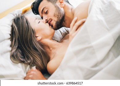 Young couple in love kissing in a bed under white blanket - Passionate lovers having romantic and intimate moments on the bed - Sex and passion concept - Focus on male face