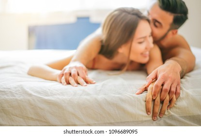 Young couple in love kissing and having sex in the bed - Passionate lovers having romantic and intimate moments in the bedroom - Concept of love, intercourse, sexual