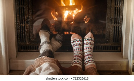 Young couple in love in knitted warm socks lying next burning fireplace at living room