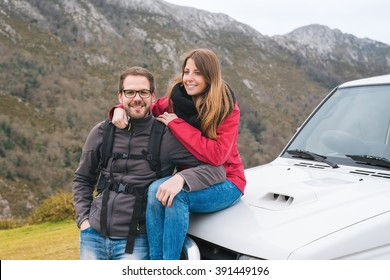 Young couple in love leaning on car, while Man looks to the camera. Hiking outdoor on vacation, enjoying relaxing rural holidays.
