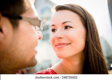 Young couple in love looking to each others eyes - outdoor in street