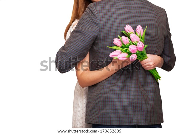 Young couple in love make a heart and hands are holding a bouquet of tulips. The concept of Valentine's Day