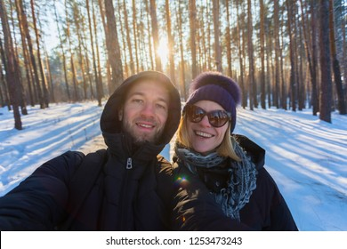 Young couple in love makes selfie in the winter snow-covered forest on the background of the bright setting sun. Walks in the open air. Travel as a lifestyle, life in motion