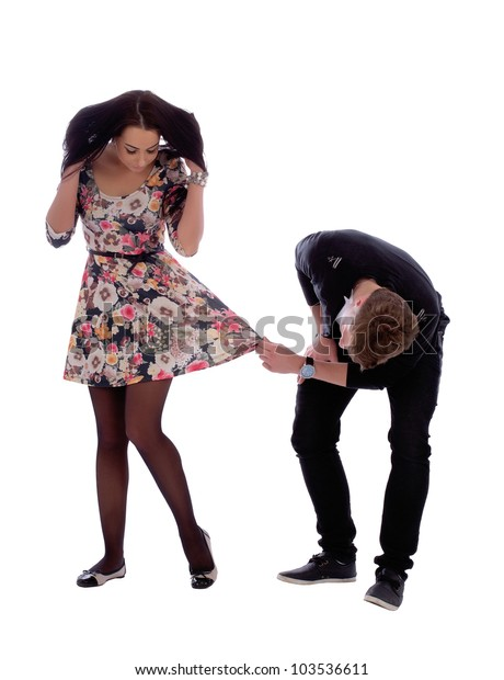 Young couple in love. Man peek under her dress om white.