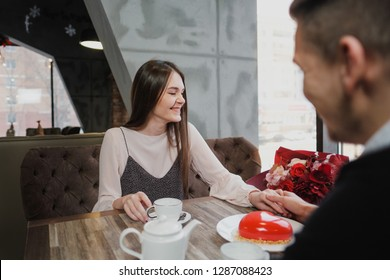 A young couple in love, a man and a woman, are sitting at a table in a cafe by the window. On the table is a teapot, cups, a bouquet of flowers and a cake in the shape of a heart. Valentine's Day.