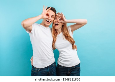 Young couple in love, man and woman in white T-shirts, rejoicing and showing two fingers, holding them near the eyes, on a light blue background