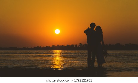 Young couple in love meet sunrise (sunset) on the banks of the lake