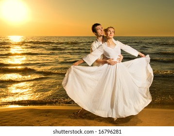 Young couple in love near the ocean at sunset