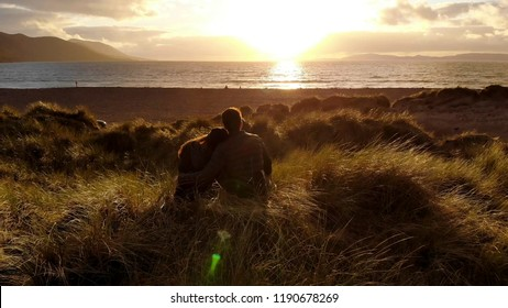 Young couple in love on the beach at sunset