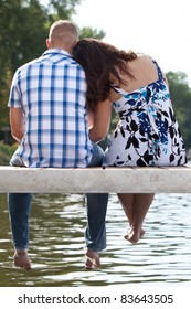 Young couple in love on pier by the lake