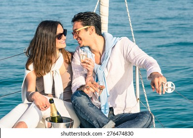 Young couple in love on sail boat with champagne flute glasses - Happy exclusive alternative lifestyle concept - Boyfriend and girlfriend flirting on luxury sailboat - Sunny afternoon color tones