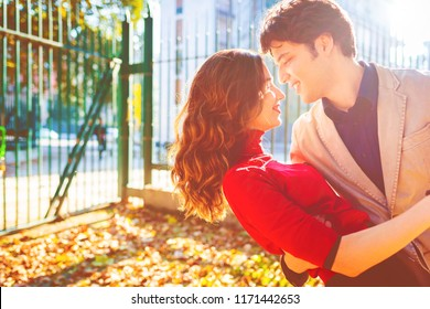 young couple in love outdoor back light hugging looking in the eye smiling - happiness, love, relationship concept