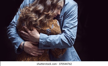 Young couple in love outdoor.  Man hugs  woman. kiss on the forehead