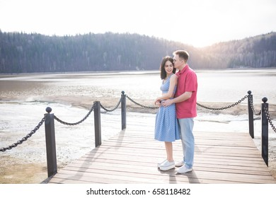 Young couple in love outdoors embracing and laughing together at lake pier.