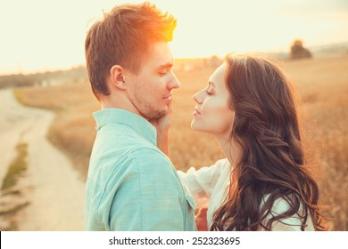 Young couple in love outdoor.Stunning sensual outdoor portrait of young stylish fashion couple posing in summer in field.Happy Smiling Couple in love.They are smiling and looking at each other