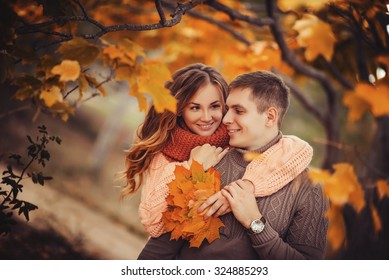 Young couple in love outdoor.Stunning sensual outdoor portrait of young stylish fashion couple posing in park in autumn