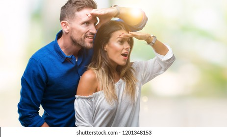 Young couple in love over isolated background very happy and smiling looking far away with hand over head. Searching concept.