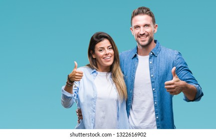 Young couple in love over isolated background doing happy thumbs up gesture with hand. Approving expression looking at the camera with showing success.