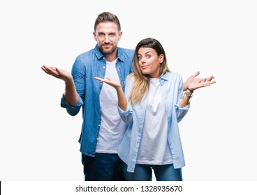 Young couple in love over isolated background clueless and confused expression with arms and hands raised. Doubt concept.