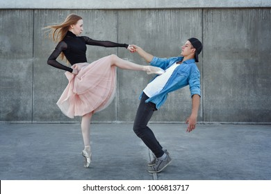 A young couple in love passionately dances on a city street. Ballerina and athlete parkour. Meshenie classical and modern dance.