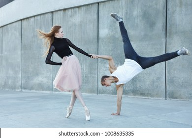 A young couple in love passionately dances on a city street. Dancer and sportsman Parkour. Balance and stunts in the dance. Meshenie classical and modern dance.
