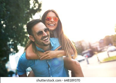 Young couple in love piggybacking in the city. Focus on girl.