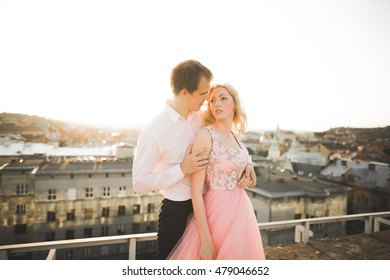 Young couple in love posing on roof with perfect city view holding hands and hugging . Beautiful sunset