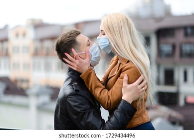 Young couple in love in protective medical mask on face outdoor at street. Guy and girl in virus protection.