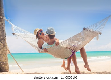 Young couple in love relaxing in a hammock by the beach