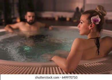 Young couple in love relaxing in a jacuzzi bath