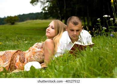 young couple in love relaxing on the summer meadow