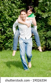 Young couple in love running over a green