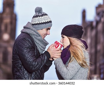 Young couple in love share hot drink in red cup on Royal Mile in Edinburgh. Two youngsters dating on Valentine's day