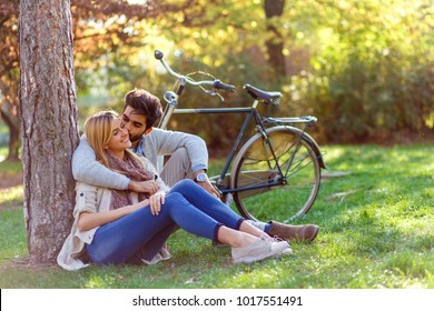 Young couple in love sitting in a autumn park leaning against a tree embracing one another.