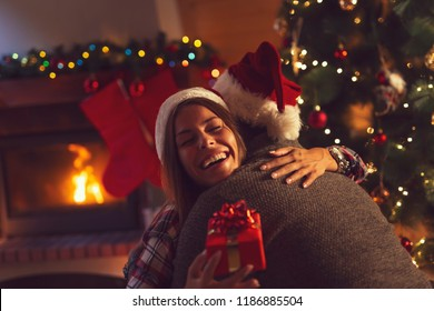 Young couple in love sitting by the fireplace and nicely decorated Christmas tree, exchanging Christmas presents