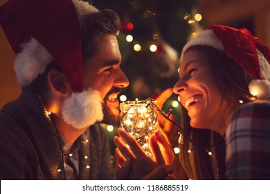 Young couple in love sitting by the fireplace and nicely decorated Christmas tree, enjoying the Christmas magic. Focus on the man