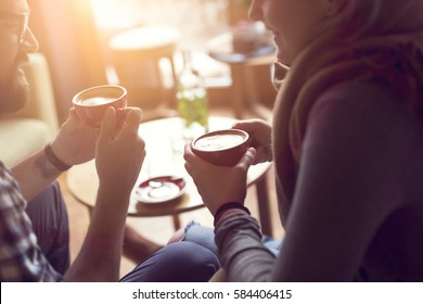 Young couple in love sitting in a cafe, drinking coffee, having a conversation and enjoying the time spent with each other. Selective focus