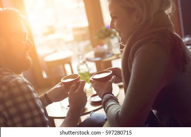 Young couple in love sitting in a cafe, drinking coffee, having a conversation and enjoying the time spent with each other. Focus on the right coffee cup