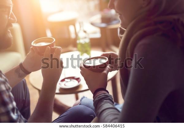 喫茶店で座り、コーヒーを飲み、会話をし、お互いに過ごした時間を楽しむ恋の若い夫婦。限定フォーカス