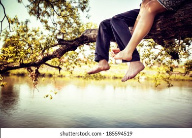 Young couple in love sitting cross-legged on a tree branch above the river in nice sunny day. Photo is colorized in warm tints.