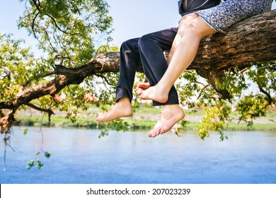 Young couple in love sitting cross-legged on a tree branch above the river in nice sunny day. Photo is effected with soft.