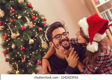 Young couple in love sitting next to a nicely decorated Christmas tree, hugging, kissing and having fun on a Christmas day. Focus on the guy