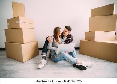Young couple in love sitting on the floor of their new apartment, planning redecoration and searching for ideas on a laptop computer and in a home decorating magazine